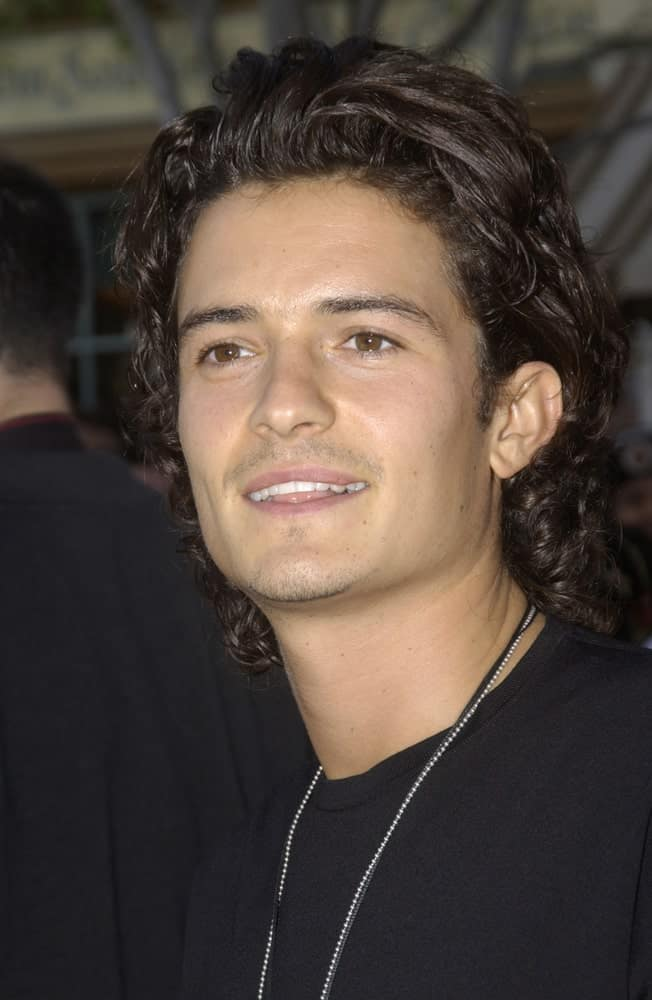 """Actor Orlando Bloom attended the world premiere of his new movie """"Pirates of the Caribbean: The Curse of the Black Pearl"""" at Disneyland, California on June 28, 2003. He came in a casual black shirt with his long tousled curly hairstyle."""