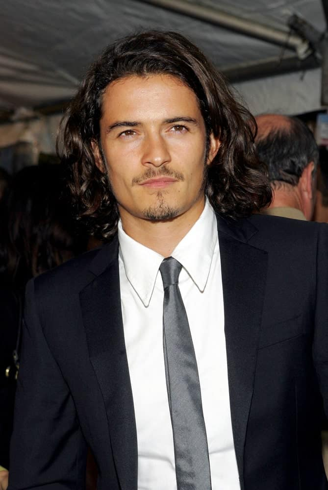 Orlando Bloom sported a side-parted long curly hairstyle and classy black suit at the