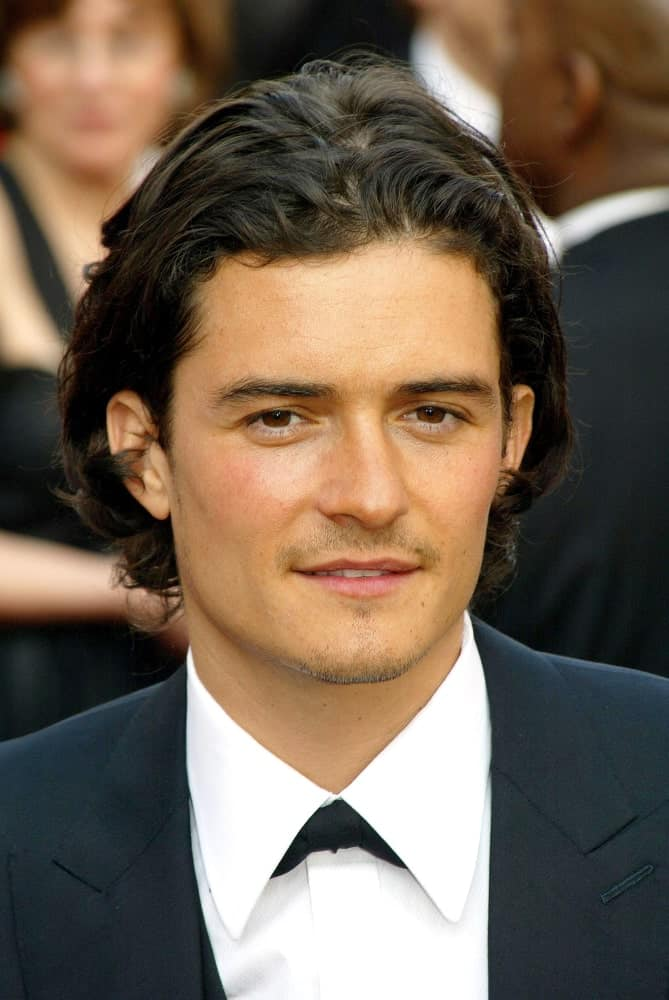 Orlando Bloom's medium-length hair was brushed-back and parted in the middle with curls at the tips on February 27, 2005 at the 77th Annual Academy Awards Oscar Ceremony in Los Angeles.