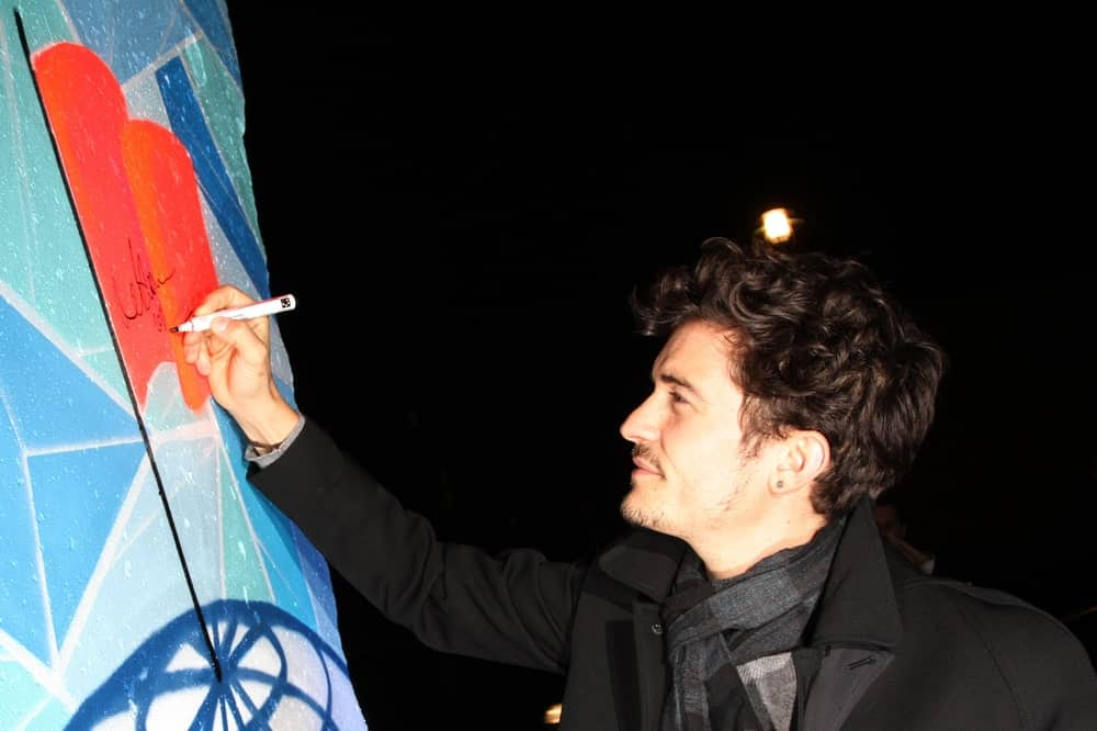 Orlando Bloom signed a piece of the former Berlin Wall at the Cinema For Peace Green Evening on November 12, 2010 in Berlin, Germany. He looked quite dreamy in his messy curls with a slight side-parted style.
