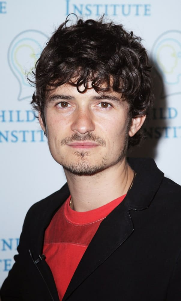 Orlando Bloom spoke at the 2010 Adam Jeffrey Katz Memorial Series Lecture Series at the Rockefeller University on June 2, 2010 in New York City. He wore a smart casual outfit with a  messy long curly fringe hairstyle and trimmed beard.