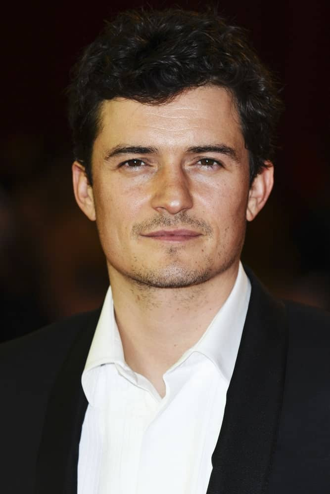 The ever dapper Orlando Bloom wore a classy suit with his short and curly hair with a wet look finish for the UK Premiere of The Three Musketeers, at Westfield, London on October 4, 2011.