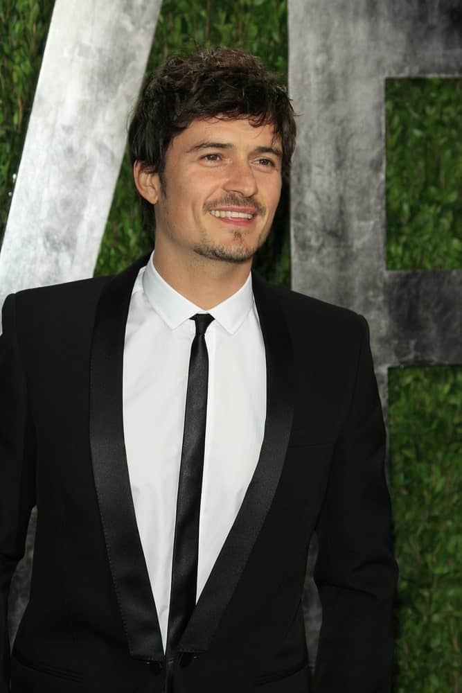 Orlando Bloom's short hair was styled into this gorgeous messy fringe hairstyle that works well with his trimmed facial hair at the Vanity Fair Oscar Party at Sunset Tower on February 24, 2013 in West Hollywood, California.