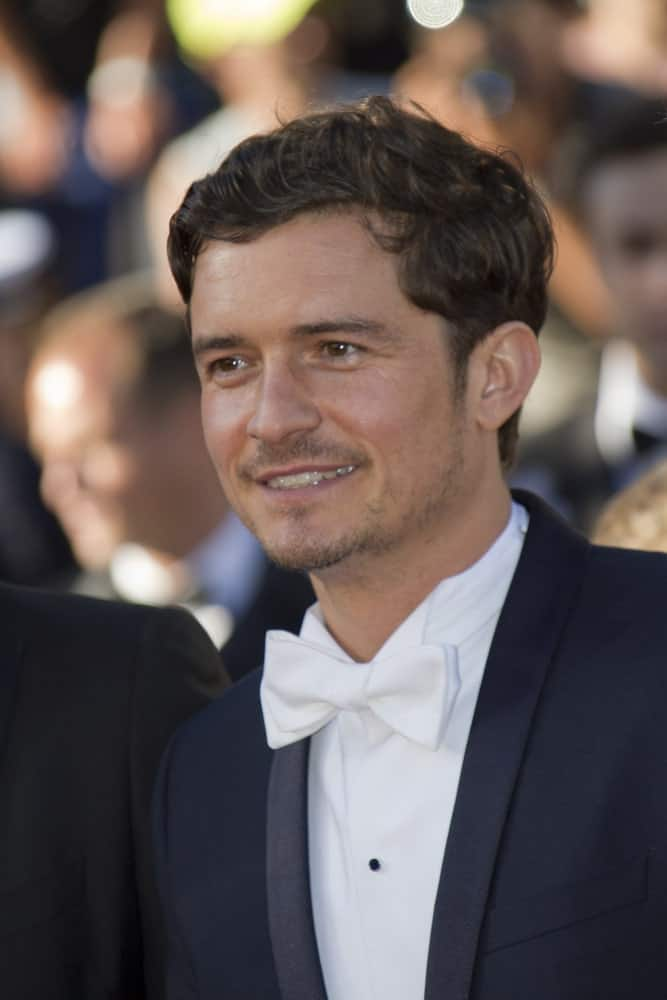 Orlando Bloom attended the Premiere of 'Zulu' and the Closing Ceremony of The 66th Cannes Film Festival at Palais on May 26, 2013 in Cannes, France. He paired his classy suit with a short side-parted curly hairstyle and five o'clock shadow.