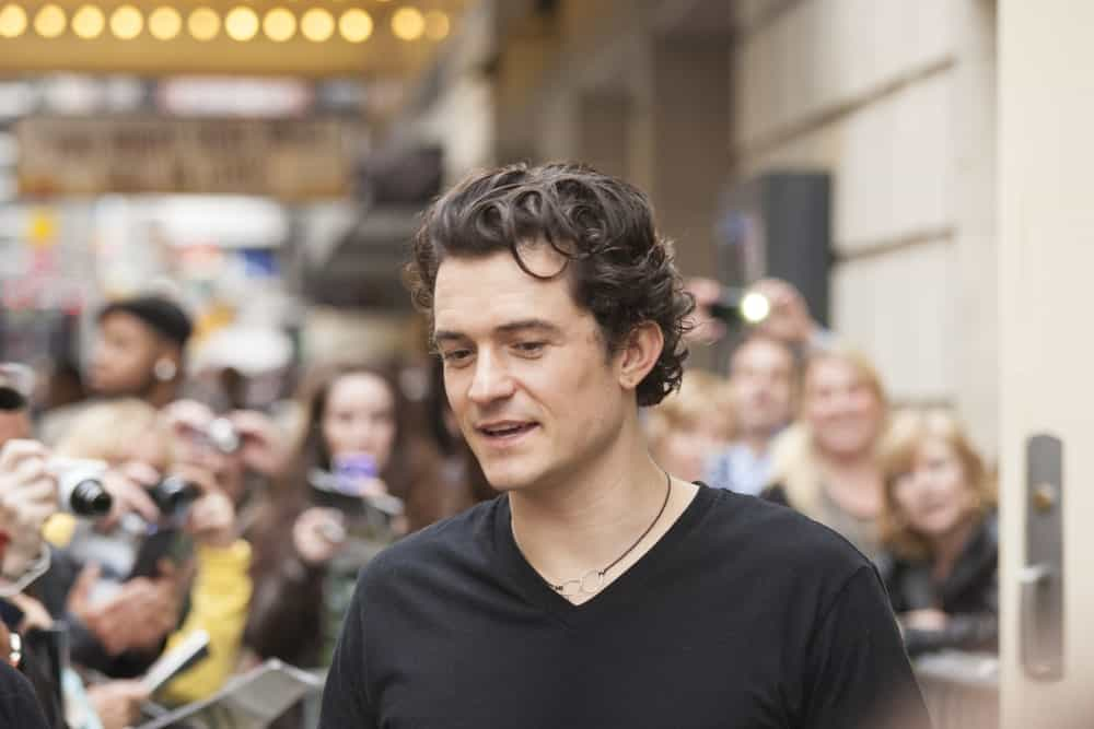 """Orlando Bloom gave autographs prior to """"Romeo and Juliet"""" performance at Richard Rogers Theater on October 9, 2013 in New York. He wore a casual black shirt with his gorgeous dark curly hair."""