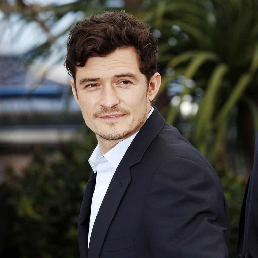 Actor Orlando Bloom attended the 'Zulu' Photo-call during the 66th Cannes Film Festival on May 26, 2013 in Cannes, France. His lovely curls were side-parted and slightly highlighted.