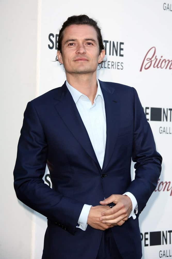 Orlando Bloom swept his long curly hair for a neat man bun hairstyle when he attended the annual Serpentine Galley Summer Party at The Serpentine Gallery on July 1, 2014 in London, England.