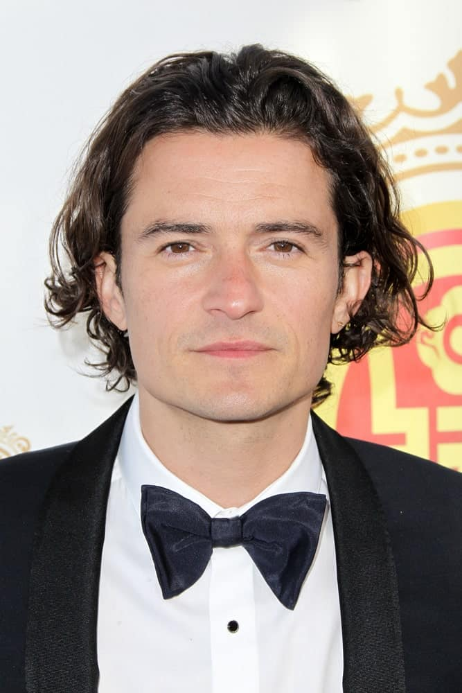 Actor Orlando Bloom's long and dark curls are on full display with his gorgeous smile and classy tux at the 2014 Huading Film Awards at The Montalban in Hollywood, California.