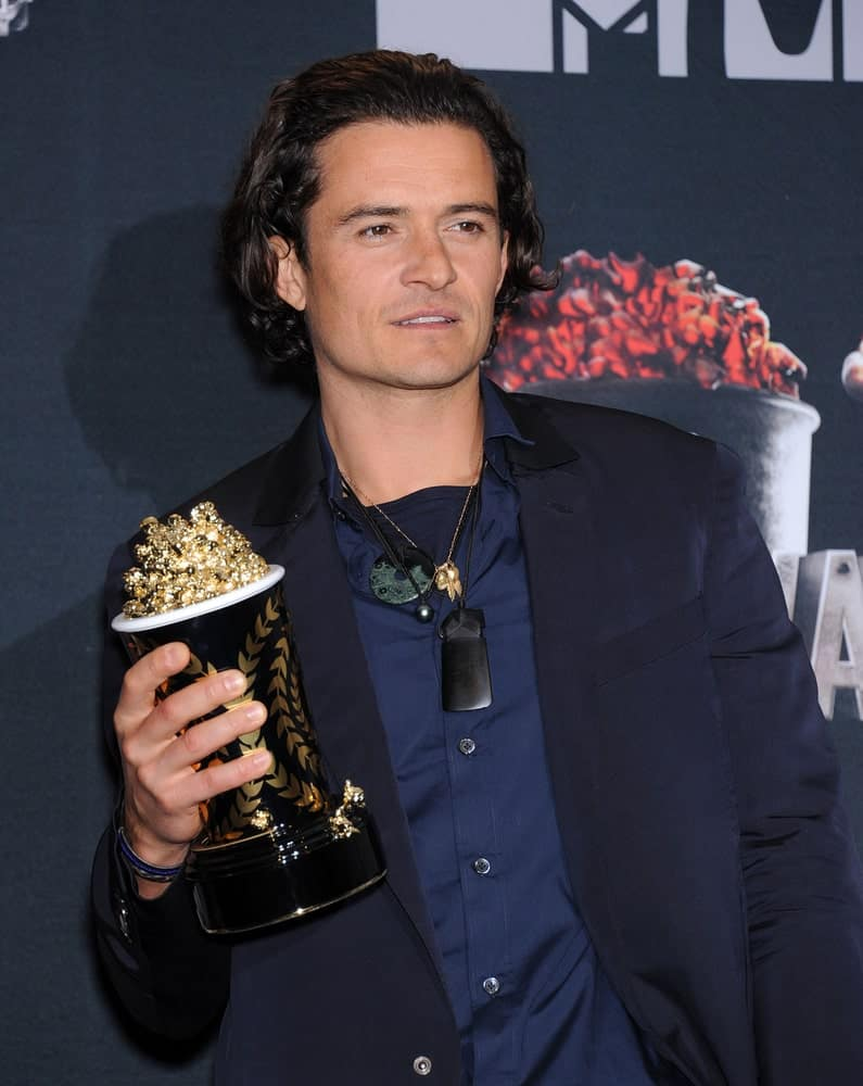Orlando Bloom's smart casual outfit was a nice complement to his long dark brushed back hairstyle at the 2014 MTV Movie Awards - Press Room on April 13, 2014 in Los Angeles, CA.