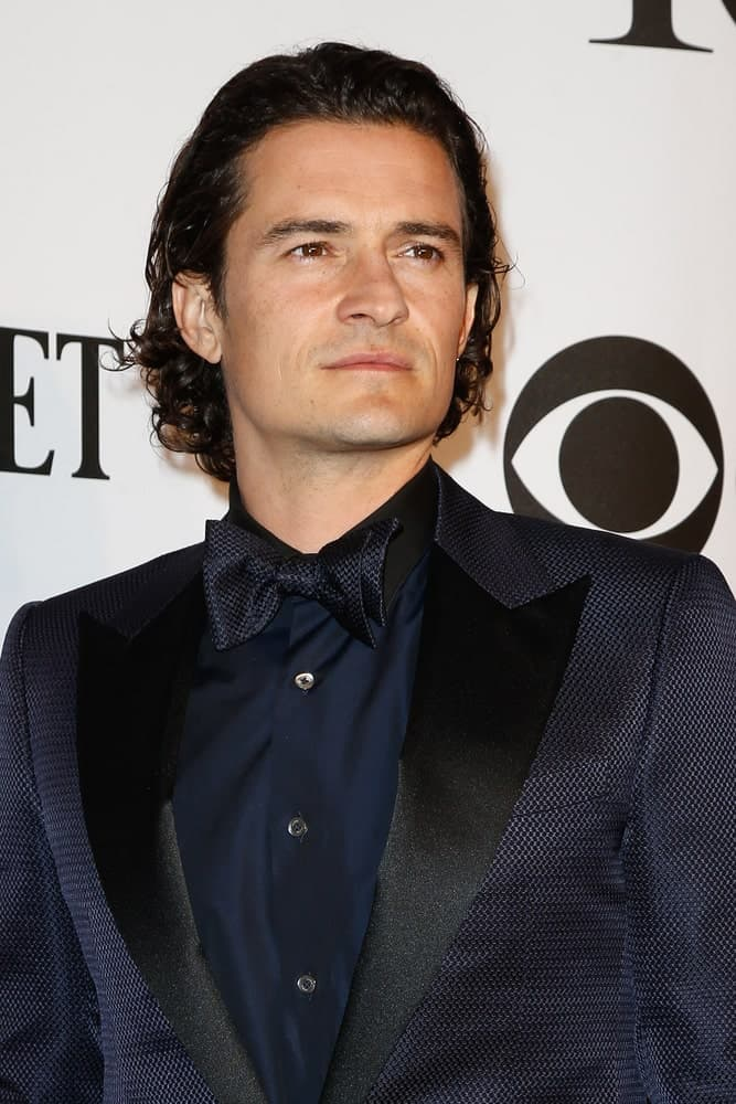 Actor Orlando Bloom sported a slicked back long and curly hairstyle when he attended the American Theatre Wing's 68th Annual Tony Awards at Radio City Music Hall on June 8, 2014 in New York City.