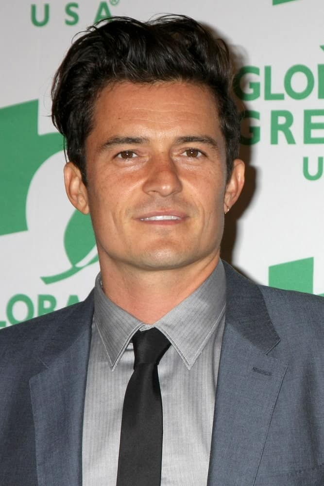 Orlando Bloom sported a messy pompadour hairstyle with his dapper gray suit at the Global Green Hosts Book Lauch of