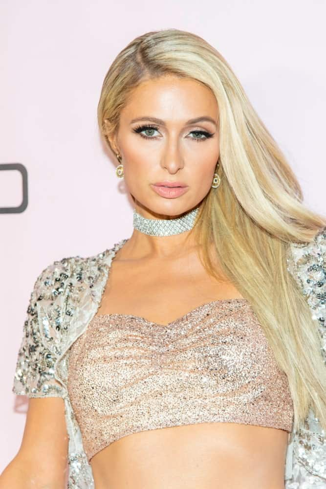 "Paris Hilton rocked a simple side-parted hairstyle with some highlights during the boohoo.com ""All That Glitters"" Launch Party on November 7, 2019. She finished the look with sparkling accessories and a glittering tube topped with a white see through blazer."