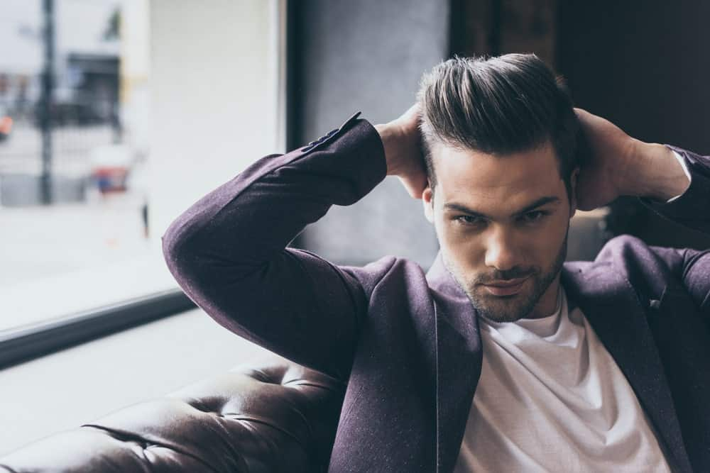 The pompadour is a classic among men's hairstyle. Here you can see a man in a white shirt and a blazer flexing his classic pompadour style.