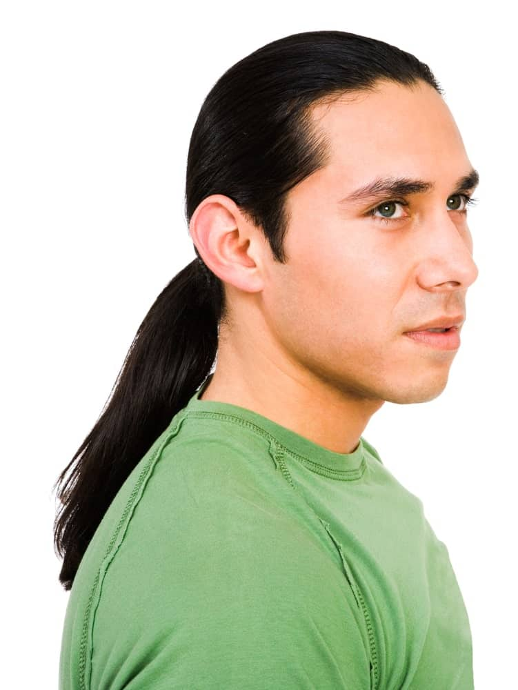 A young man in green T-shirt. He has a long black hair in ponytail style.