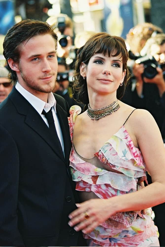 Sandra Bullock and Ryan Gosling attended the 'Murder by numbers' Premiere at the Grand Theatre Lumiere during the 55th Cannes film festival on May 24, 2002 in Cannes, France. Gosling had a side-parted dyed black hairstyle to go with his black suit.