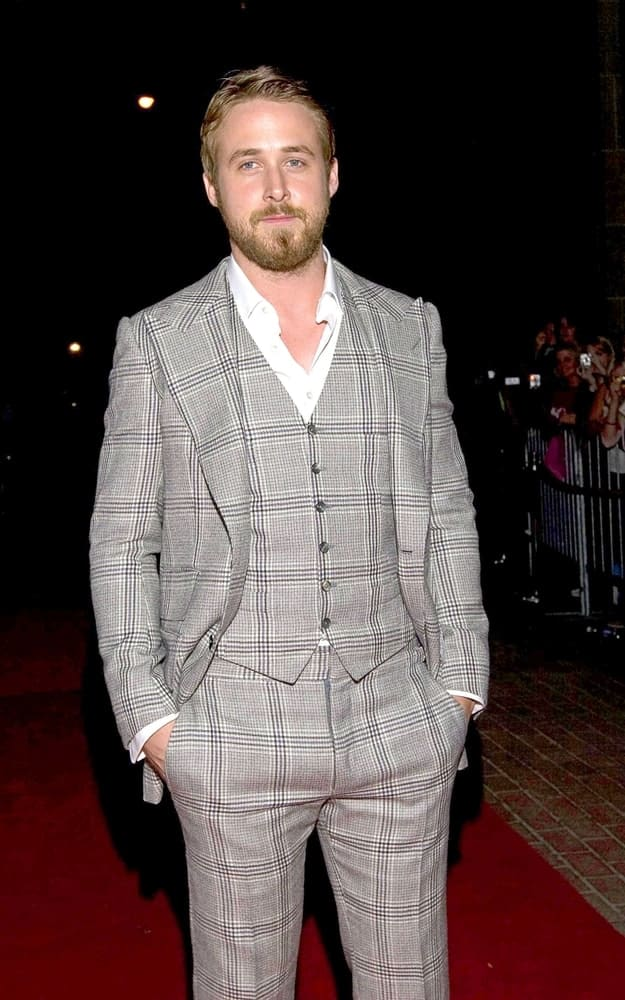 Ryan Gosling wore a full scruffy beard with a side-parted sandy blond hairstyle at