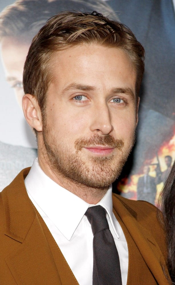 On January 7, 2013, Ryan Gosling wore a classy tan suit that complements his dark brown hair with a stylish slick side-part finish at the Los Angeles premiere of 'Gangster Squad' in Los Angeles.