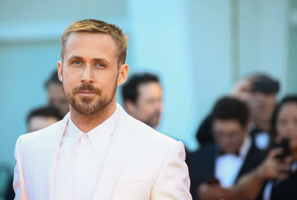 Ryan Gosling walked the red carpet of the 'First Man' screening during the 75th Venice Film Festival on August 29, 2018 in Venice, Italy. He wore an all-white suit with his short sandy blond hair in a side-parted crew cut fade hairstyle.