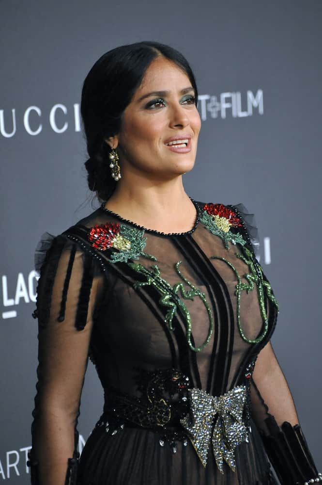 Actress Salma Hayek Pinault was at the October 29, 2016, LACMA Art+Film Gala at the Los Angeles County Museum of Art. She had her brunette hair styled to a classy low bun to match her black dress with shiny details.