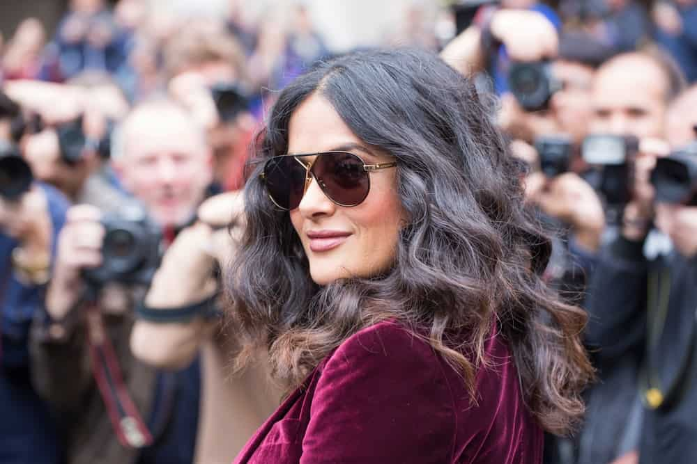 The actress Salma Hayek was at the Stella McCartney fashion show in Paris last October 2, 2017. She was seen wearing a red velvet outfit, a confident smile and tousled wavy hair with highlights.