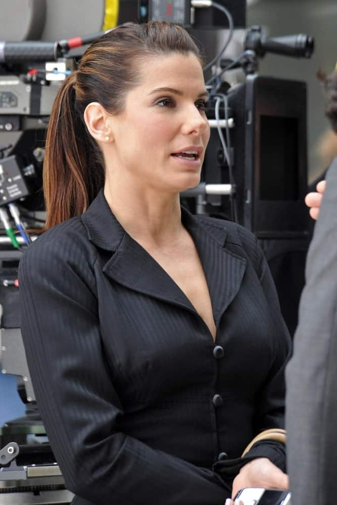 """Sandra Bullock was seen on location for """"The Proposal"""" filming in New York last June 06, 2008. Her power suit outfit was paired with a neat and slick highlighted ponytail."""