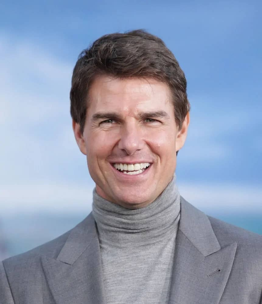 "Tom Cruise flashed his signature smile at the ""Oblivion"" US Premiere on April 10, 2013, in Hollywood, CA with a jagged short hairstyle to match his turtle neck outfit."