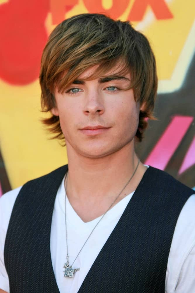 Zac Efron during the 2007 Teen Choice Awards, sporting a side-swept bangs hairstyle along with a white shirt and a vest.
