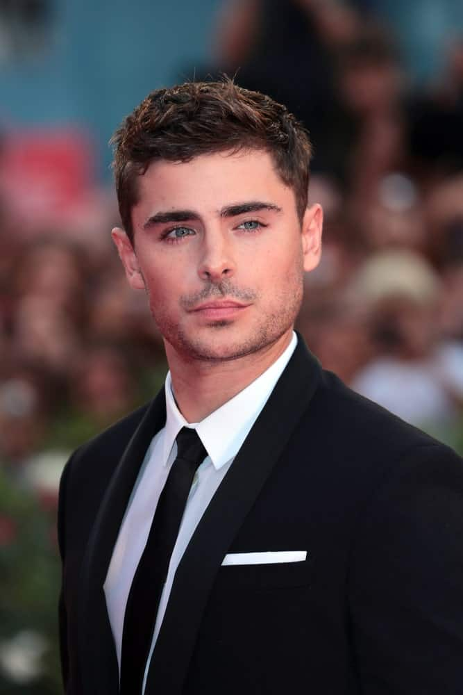Zac Efron in a classic black suit with a stylish hairstyle, seen at the Venice Film Festival on August 31, 2012.