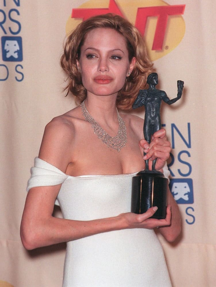 "On March 7, 1999, actress Angelina Jolie was at the Screen Actors Guild Awards where she won Best Actress in a TV Movie for ""Gia"". She was wearing a white lovely dress with her hair dyed into a sandy blond tone and styled into a short and layered wavy look."
