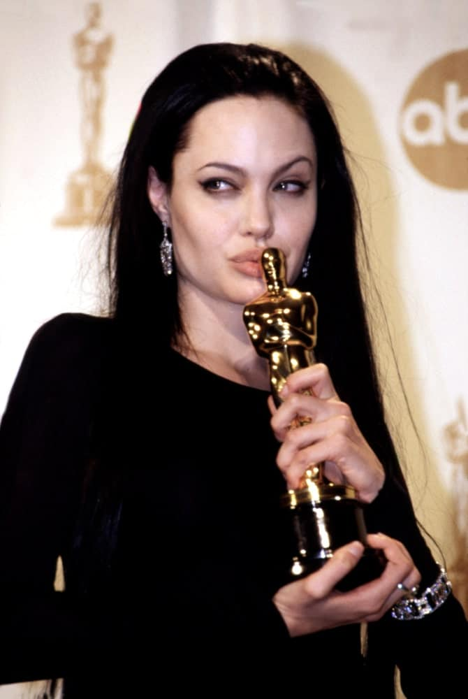 Angelina Jolie was beaming with pride in her Academy Award win for her movie GIRL INTERRUPTED way back in March of 2000. She was wearing an all-black outfit to go with her straight and loose long hairstyle that is jet black.