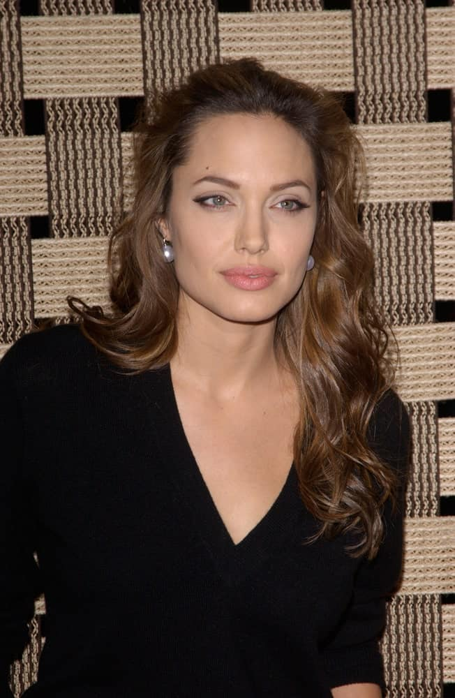 On December 2, 2004, actress Angelina Jolie was at the Los Angeles premiere of Hotel Rwanda in Los Angeles, CA. She wore a simple black casual outfit with her long and tousled wavy hairstyle.