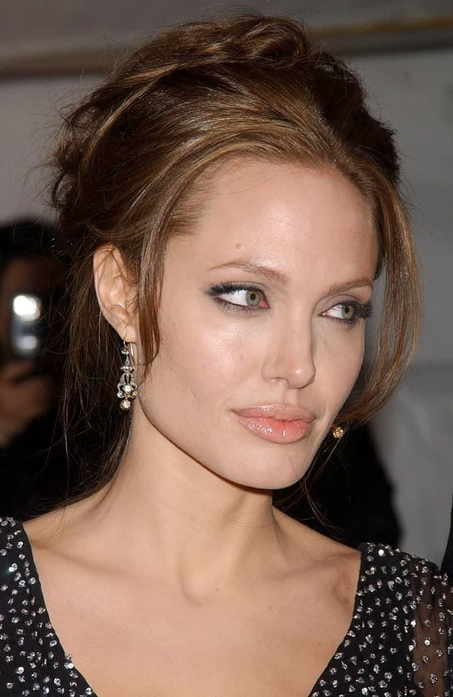 Angelina Jolie's lovely black bejeweled dress paired quite well with her loose and messy upstyle hair with tendrils and bangs at the Premiere of THE GOOD SHEPHERD in Ziegfeld Theatre, New York on December 11, 2006.