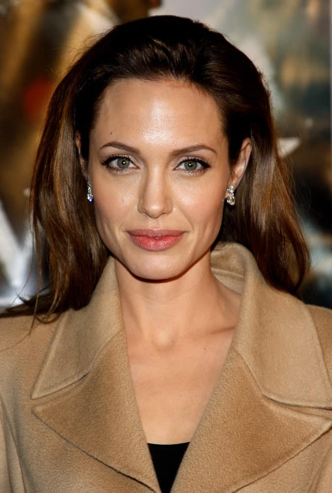 "Angelina Jolie wore a big brown tan jacket with her long and loose silky straight hair with highlights at the Los Angeles Premiere of ""Beowulf"" held at the Westwood Village Theater in Westwood, California, the United States on November 5, 2007."