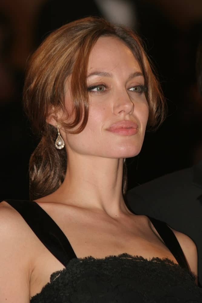 Angelina Jolie's beautiful face was framed well by her long and loose bangs that is paired with her ponytail hairstyle when she attended the screening of A Mighty Heart produced by Brad Pitt with Angelina Jolie on May 21, 2007, in Cannes, France.