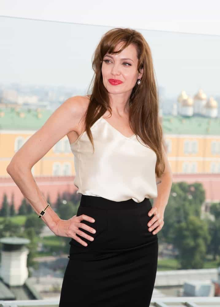 """Actress Angelina Jolie attended the premiere of the movie """"Salt"""" at the Ritz Hotel on July 25, 2010, in Moscow, Russia. She wore a smart casual outfit to match her tousled long brown hair with layers and side-swept bangs."""