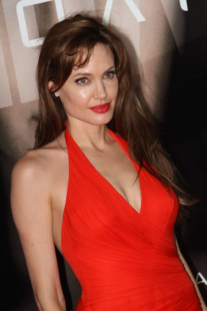 American Actress Angelina Jolie attended the premier of her new movie 'Salt' in Oktyabr Cinema Hall on July 25, 2010, in Moscow, Russia. She was stunning in her red dress, red bold lips and long layered hairstyle with bangs.