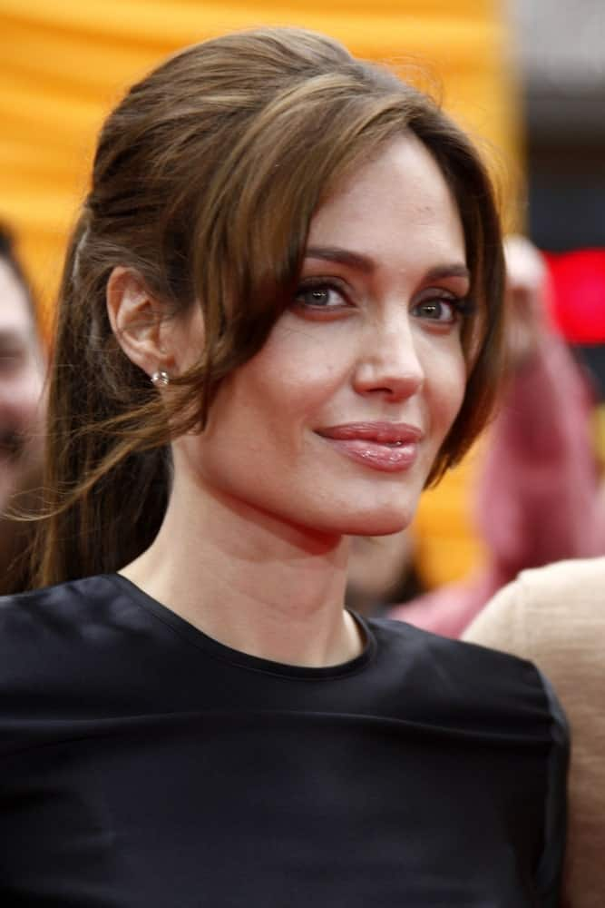 "Angelina Jolie paired her simple black outfit with a charming ponytail hairstyle paired with long curtain bangs at the ""Kung Fu Panda 2"" Los Angeles Premiere at Grauman's Chinese Theatre on May 22, 2011, in Los Angeles, CA."