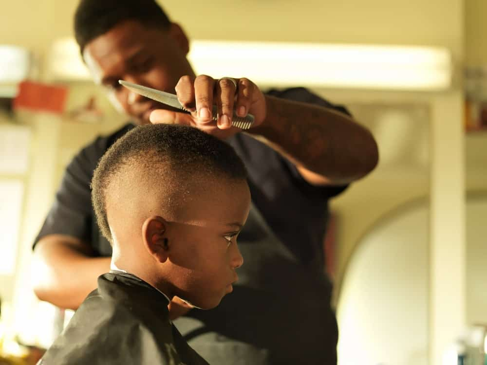 A little kid having his hair cut by a barber.