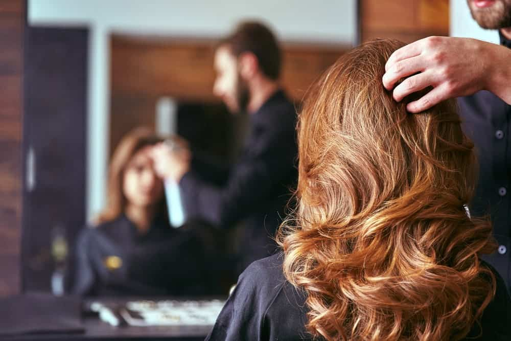 A stylist working on a woman's long wavy hair.