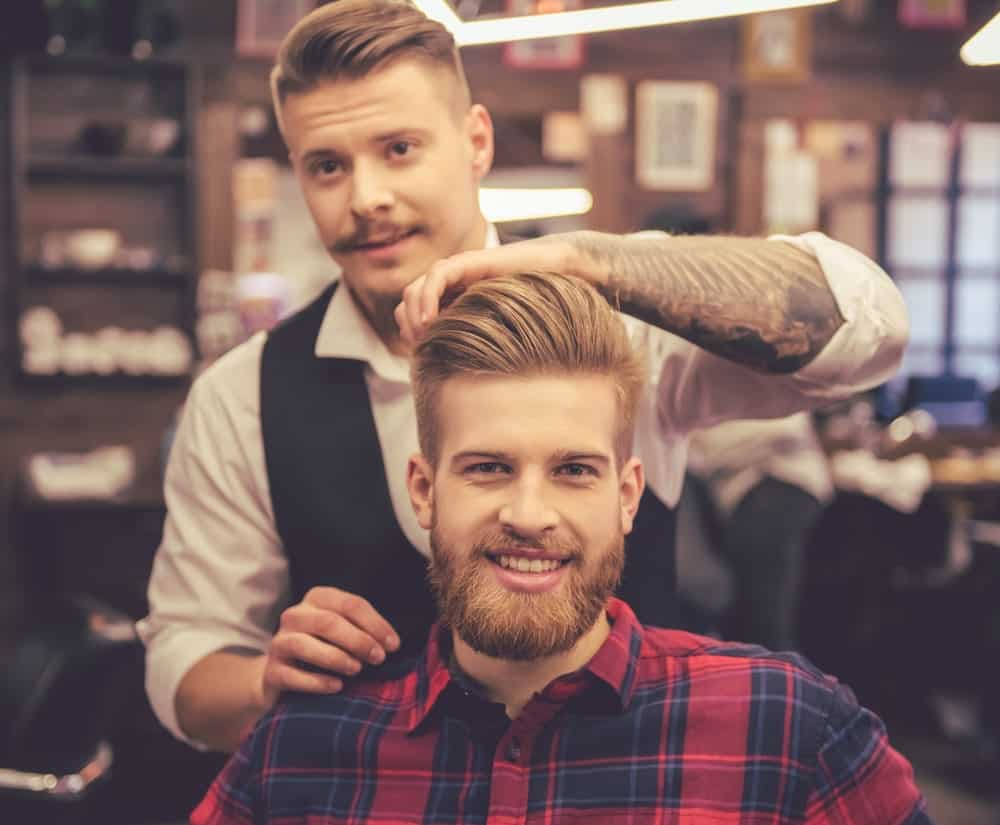 A bearded man having his done by a barber.