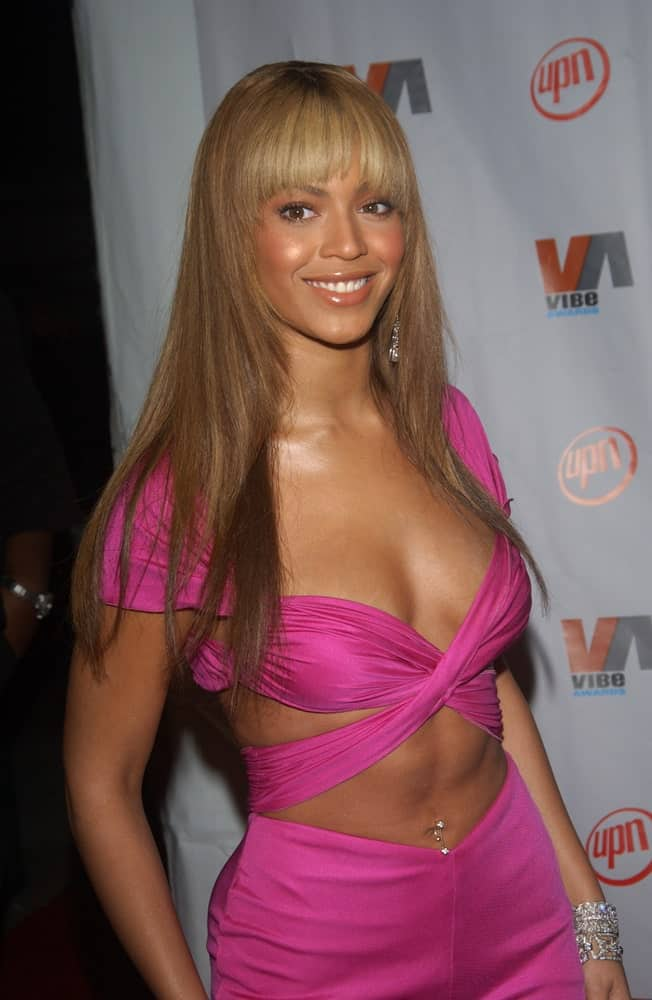 Beyonce in a hot pink outfit at the 2003 Vibe Awards in Santa Monica, CA held on November 20, 2003. She finished the look with her straight layered hair incorporated with eye-skimming bangs.