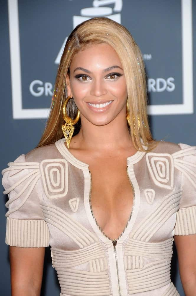 Beyonce Knowles looking sleek in a blonde straight hairstyle with a deep side part at the 52nd Annual Grammy Awards on January 31, 2010. She finished the look with a textured geometric dress and gold statement earrings.