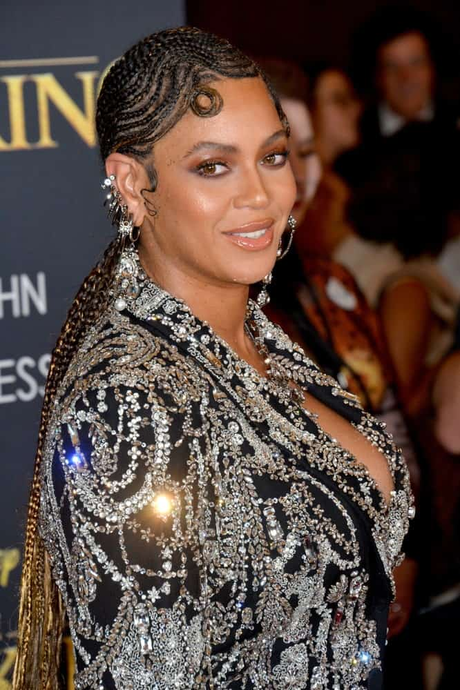"""Beyonce Knowles shines in an embellished dress that perfectly goes with her swirling cornrows during the world premiere of Disney's """"The Lion King"""" at the Dolby Theatre on July 10, 2019."""