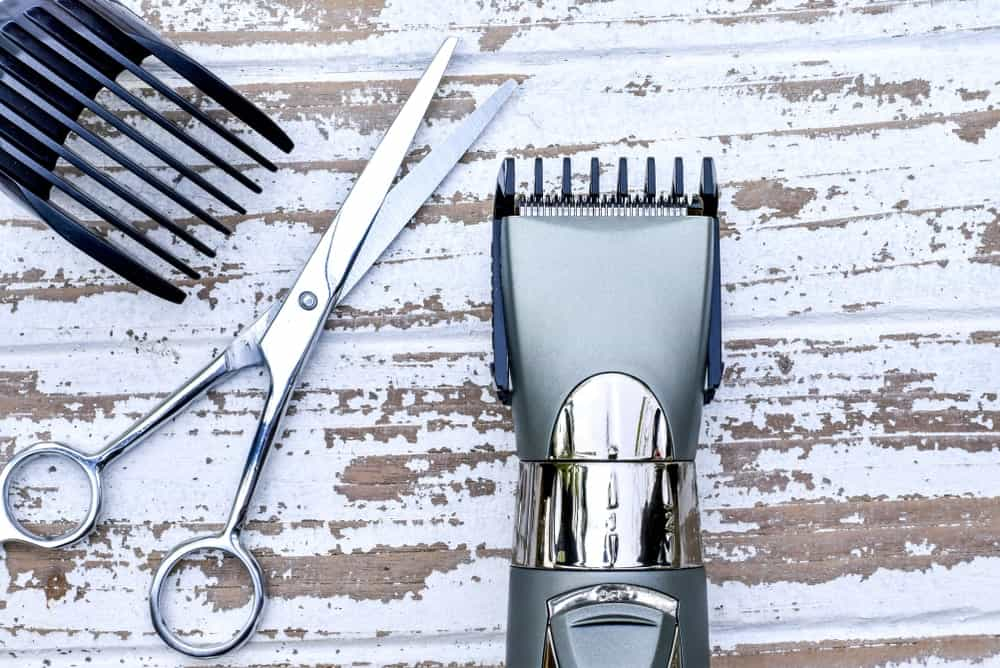A chrome hair clipper with a pair of chrome scissors on a wooden surface.