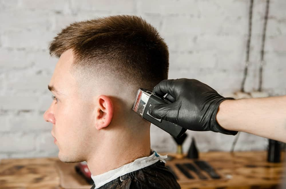 A man having a fade haircut with the use of a hair clipper.