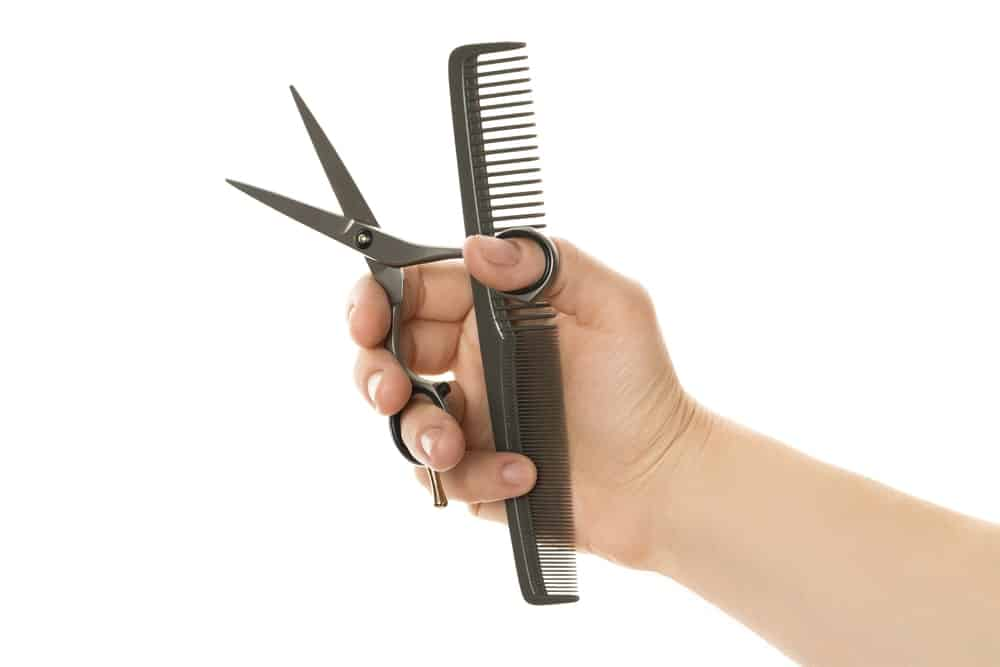 A pair of scissors and a comb held in hand.