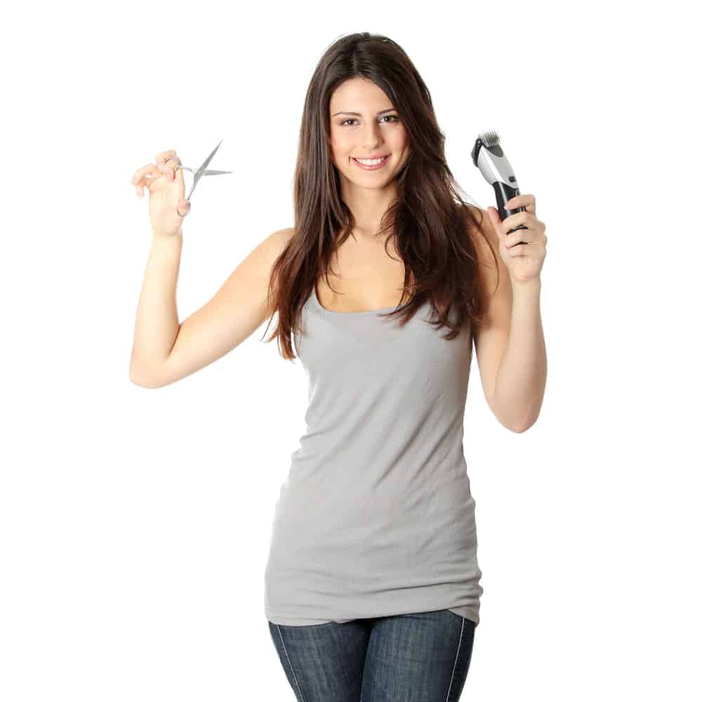 A female hair stylist holding a pair of scissors and clippers on each hand.