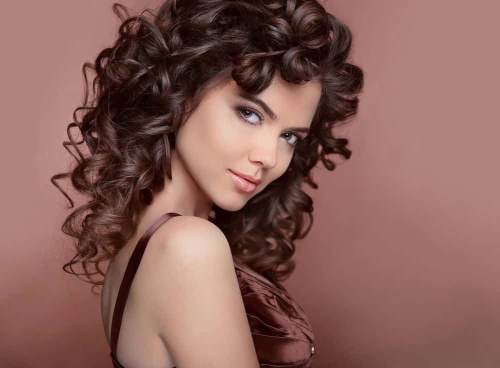 A pretty brunette woman with long curly hair.