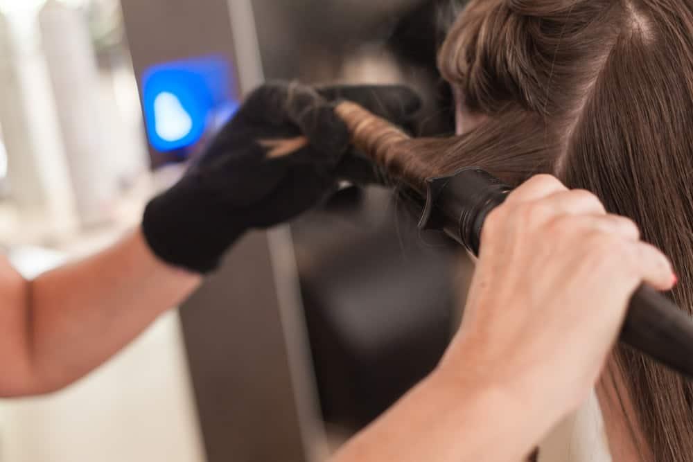 A hairdresser using a curling wand on a brunette woman.