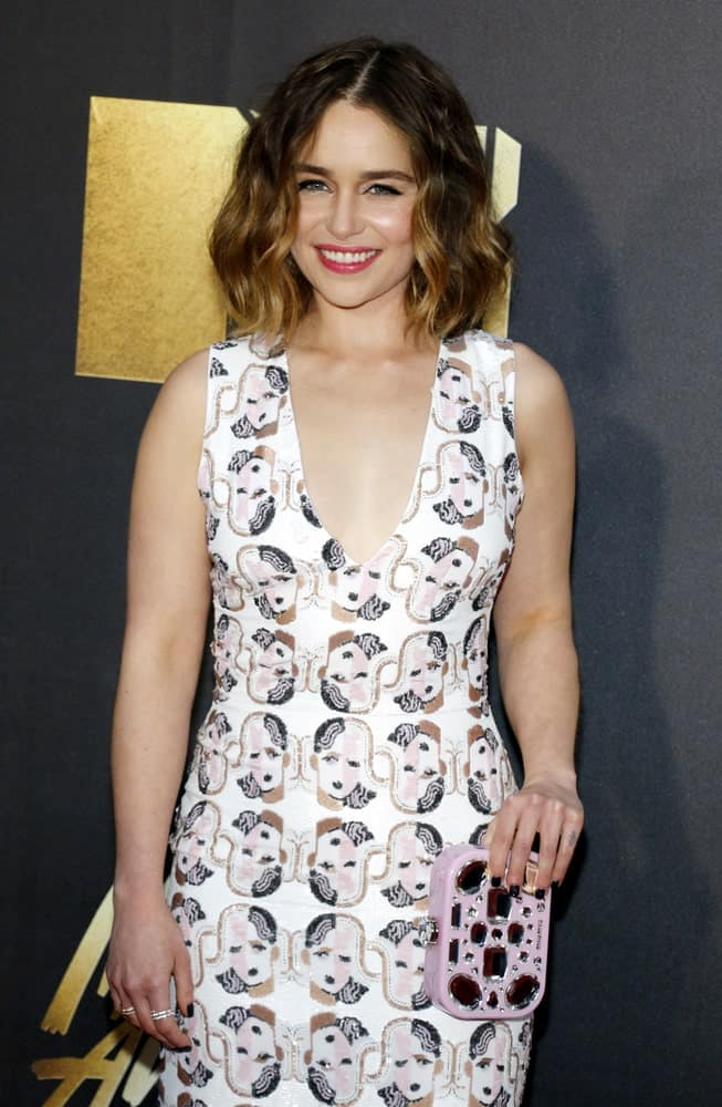 Emilia Clarke with medium-length wavy hair at the 2016 MTV Movie Awards. She looks very dazzling and classy in her white printed dress.